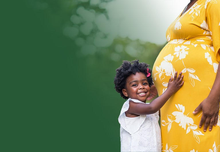 African American pregnant woman with her young daughter hugging her belly.