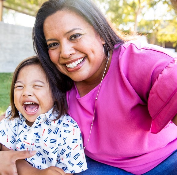 Hispanic mom and child smiling