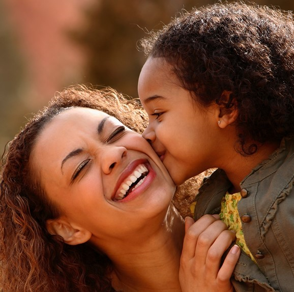 Child kissing mother on cheek